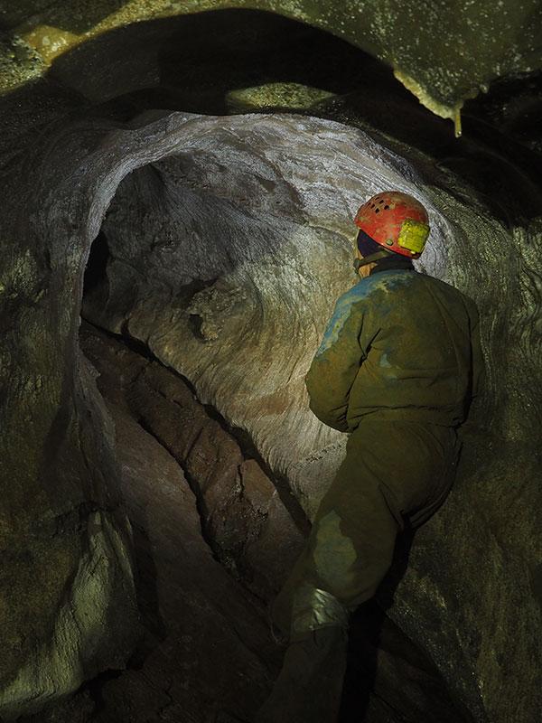 Bilde av en person som er på vei inn i ei grotte